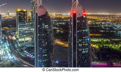 Skyline view of the buildings of Sheikh Zayed Road and DIFC night timelapse in Dubai, UAE. Illuminated skyscrapers in financial centre aerial view from above