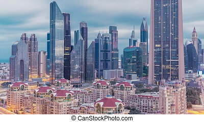 Skyline view of the buildings of Sheikh Zayed Road and DIFC night to day transition timelapse in Dubai, UAE. Illuminated skyscrapers in financial centre aerial view from above in downtown
