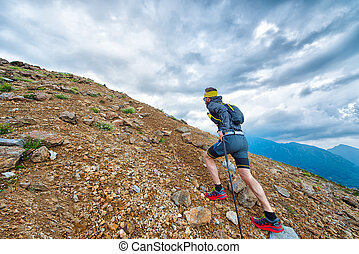 Skyrunner athlete while training in the mountains with sticks
