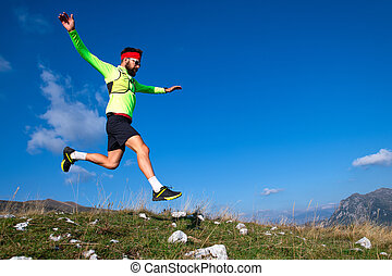 Skyrunner during a downhill jump in mountain meadows