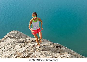 Skyrunner girl runs on a stony back over a lake