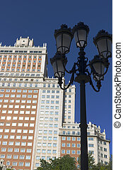 Skyscraper, called Spain Building in the Spain Square. Madrid. Ancient Style Streetlights. The Spain Building is one of the tallest buildings in Madrid, Spain. It is one of the better examples of 20th
