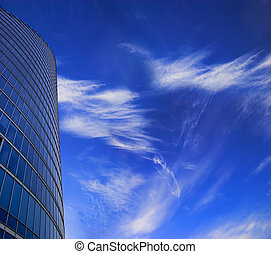 Office skyscraper facade on deep blue sky with white clouds. Place for copy space.