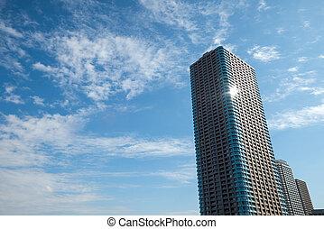 Skyscraper reflecting sunlight under blue sky with cloud