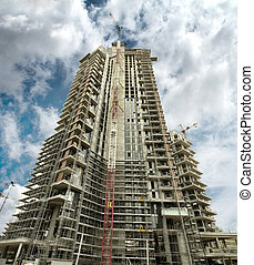 skyscraper under construction with crane and cloudy sky