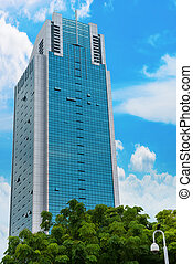 Skyscraper with blue sky and and green trees