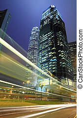 Skyscraper with traffic light and cars motion blurred in Hong Kong