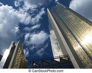 2 skyscrapers against a blue sky with clouds