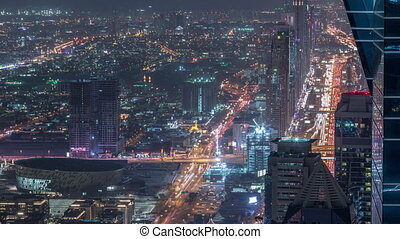 Skyscrapers on Sheikh Zayed Road and DIFC aerial night timelapse in Dubai, UAE. Traffic on a highway near Financial Centre from business bay rooftop