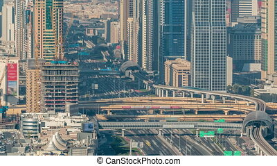 Skyscrapers on Sheikh Zayed Road and DIFC aerial timelapse in Dubai, UAE. Traffic on a highway and intersection near Financial Centre at evening before sunset