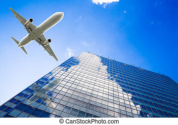Skyscrapers with a flying airplane against blue sky