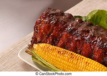 Slab of barbeque ribs with ear of roasted corn