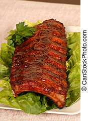Slab of ribs resting on lettuce - A slab of ribs resting on...
