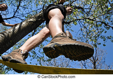 Girl balancing on the slackline in the outdoor