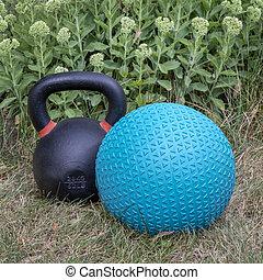 slam ball and iron kettlebel in backyard