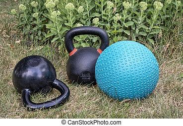 slam ball with iron kettlebels in backyard
