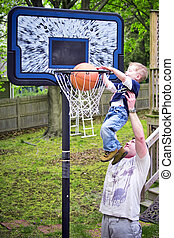 Slam dunk - Adult helping boy score a basketball shot