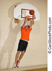 Slam Dunk - Young man makes a basketball slam dunk. Motion...