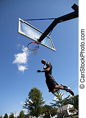 Slam Dunking a Basketball - A young basketball player...