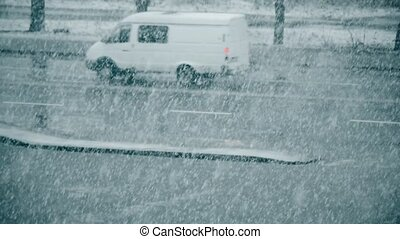 Slanting snow falling on background of blurred road -...