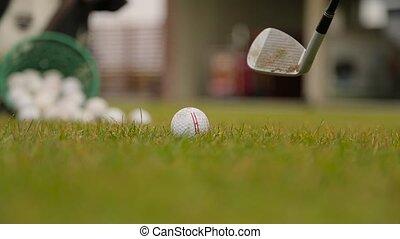 Slashing at the ball in a golf closeup.