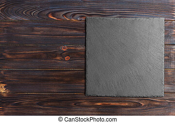 Slate board over old wooden background with copy space