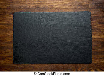 Slate over old wooden background top view