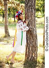 Slav girl with wreath at park.