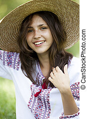 Slav teen girl at green meadow in national ukrainian clothing.