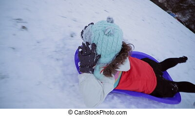 Sledding Down the Hill - Little girl is lying on her belly ...