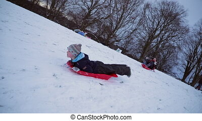 Sledding Like a Penguin - Little boy is lying on his belly ...