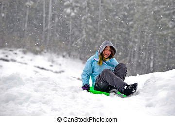 Sledding on a saucer - Teenage girl sledding in the snow on...