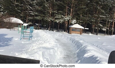 Sledding on a wooden, snow-covered slide in winter at the recreation center.