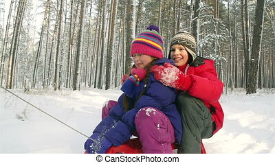 Boy and girl sledding together, boy falling off the sled