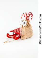 Sledge and Candy Canes in Jute Sack isolated on White