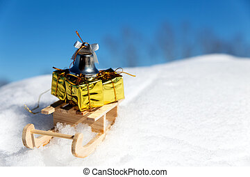 sledge with little gifts and bell in the snow