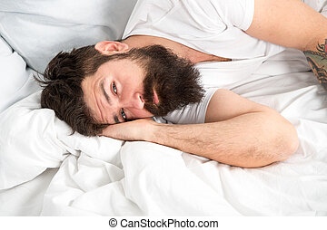 Sleep disorders concept. What a long night. Man bearded hipster having problem with sleep. Guy lying in bed try to relax and fall asleep. Relaxation techniques. Violations of sleep and wakefulness