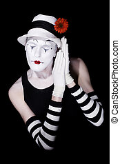 Sleep theatrical clown in a white hat and striped gloves on...