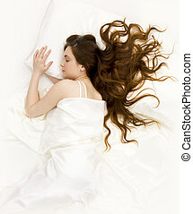 View of pretty young female lying in bed and having rest