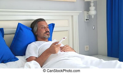 Sleepiness man in bed room watching television