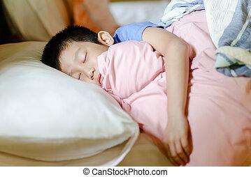 Sleeping Asian boy on bed.