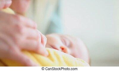 Sleeping baby being held in a blanket