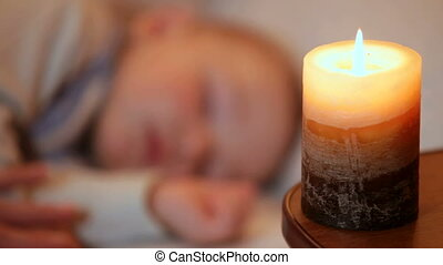 Sleeping baby boy in the candlelight closeup