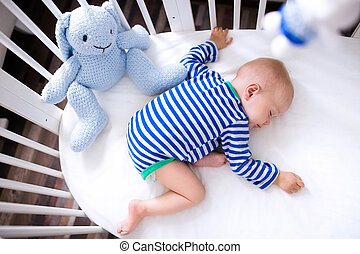 Sleeping baby boy in white crib