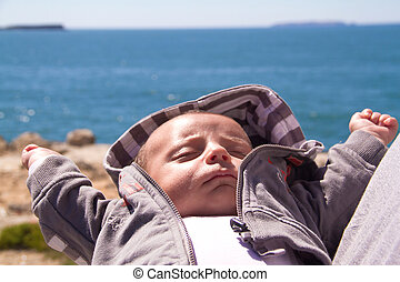sleeping baby close to sea