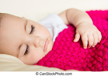Sleeping baby covered with knitted blanket - Closeup...