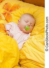 sleeping baby girl in big bed