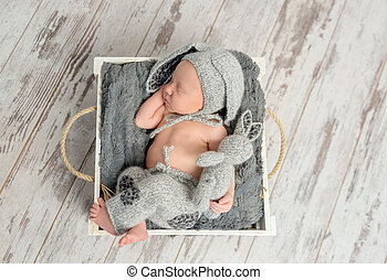 sleeping baby in gray panties and hat with hare ears