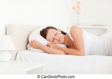 Sleeping beautiful woman lying on a bed