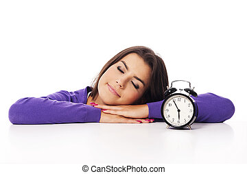 Sleeping beautiful woman with alarm clock
